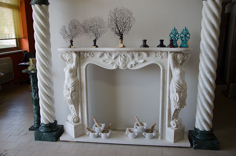 Caryatids. Fireplace with two lateral female sculptures, representing two classic caryatids and rich floral ornament entirely made by hand in white Carrara marble. The rather large fireplace is suitable for installation in large rooms.