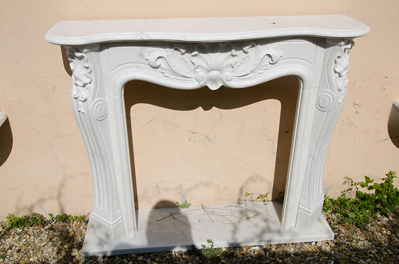 Shell and Garland Fireplace. Fireplace in white Carrara marble in Louis XVI style revisited and enriched by a garland that surrounds the classic shell of the French style. A simple fireplace but with a graceful decoration that embellishes it and makes it suitable for any environment.