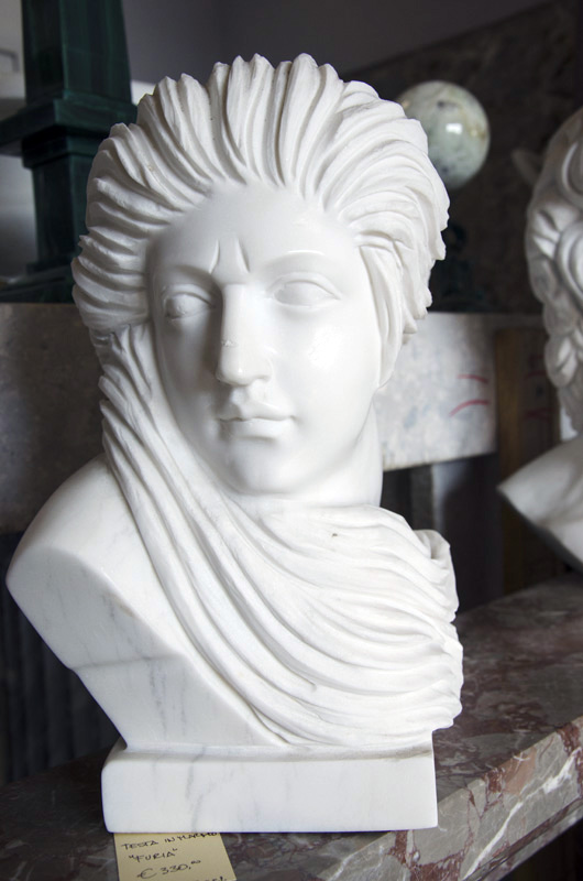Carrara white marble head depicting a woman with hair in the wind with a frowning expression.