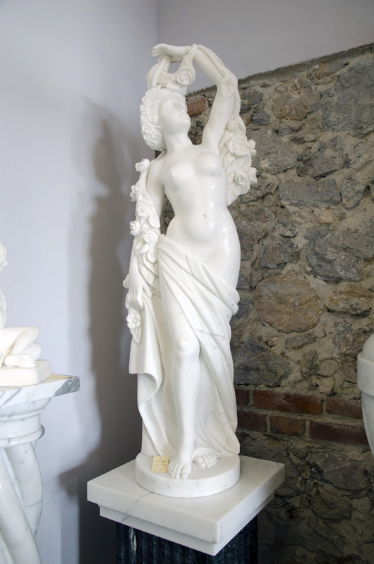 Finely hand-carved statue depicting Spring in white statuary marble. The flower garland that surrounds the young goddess enhances the beauty and value of the sculpture by highlighting the great skill of the sculptor. It is possible to redo it in other dimensions on request.
