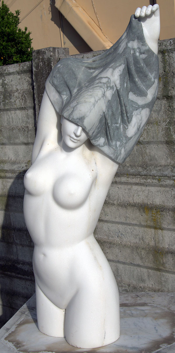 Statue of a woman in the act of removing her statuary white marble and mottled green marble dress. The subject of the statue is contemporary and carried out with the essential lines typical of modern sculpture. The color of the marble of the garment, so finely finished as to give the sensation of lightness, can be replaced by other colored marbles on request.