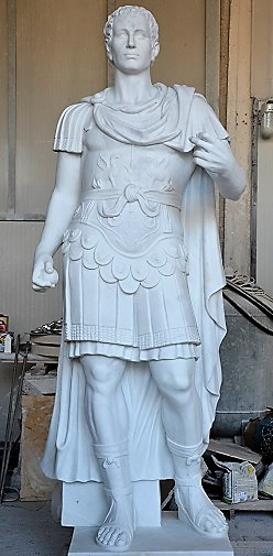Copy of Roman general, probably Julius Caesar, in white marble with long cloak and typical shoes in frontal position.